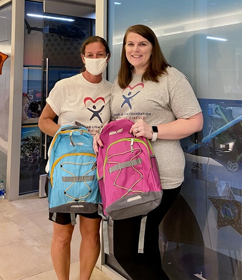 Program Assistant Lara Zdanowicz (left) and Executive Director Jessica Stanfield (right) of the Guardian ad Litem Foundation, 20th Judicial Circuit, hold backpacks provided to area students during the Back to School with the Blue event in July.